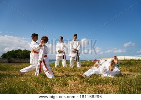 School Teachers And Children At Karate Lesson Near The Sea