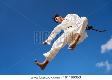 Young people athlete sport activity combat and extreme sports. Hispanic man exercising in karate and traditional martial arts jumping mid-air in the sky