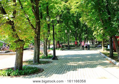 Chernihiv / Ukraine. 28 August 2016: people walk on the wide footpath in the summer park with big green trees.  28 August 2016 in Chernihiv / Ukraine.