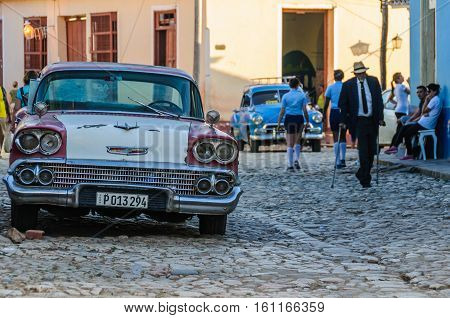 TRINIDAD, CUBA - MARCH 23, 2016: Old car and a local manon the cobblestone streets in the UNESCO World Heritage old town of Trinidad Cuba