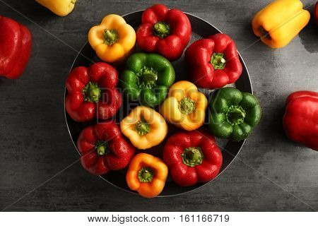 Red, green and yellow sweet bell peppers on table, top view