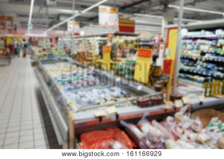 Blurred view of shelves with food stuff in supermarket