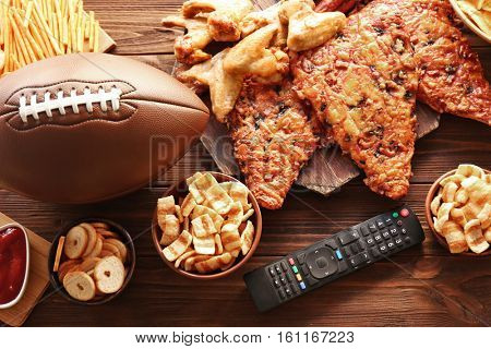 Tasty snacks, remote control and rugby ball on wooden table