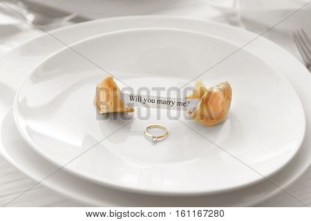 Offer of marriage with fortune cookie and ring on white plate closeup