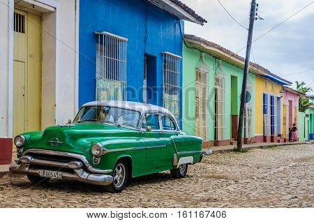 TRINIDAD, CUBA - MARCH 23, 2016: Green oldschool car on the cobblestone streets in the UNESCO World Heritage old town of Trinidad Cuba