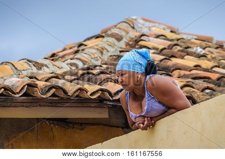 TRINIDAD, CUBA - MARCH 23, 2016: Local woman watching in the UNESCO World Heritage old town of Trinidad Cuba