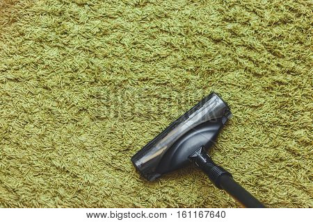 house cleaning concept. The head of a vacuum cleaner brush on the green carpet the top view.