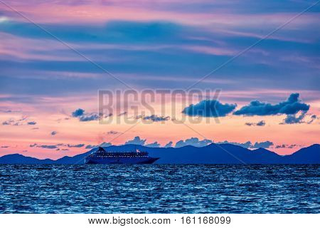 Vacation cruise background - sunset sea with cruise ship. Andaman sea, Thailand