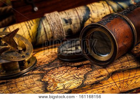 Travel geography navigation concept background - old vintage retro compass with sundial, spyglass on ancient world map