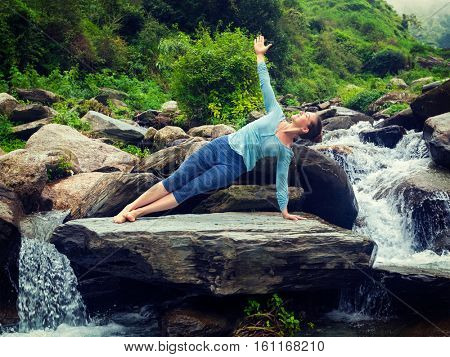 Yoga outdoors - beautiful sporty fit woman doing yoga asana Vasisthasana - side plank pose at tropical waterfall. Vintage retro effect filtered hipster style image.