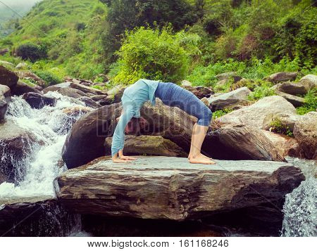 Yoga outdoors - young sporty fit woman doing Ashtanga Vinyasa Yoga asana Urdhva Dhanurasana  - upward bow pose at tropical waterfall. Vintage retro effect filtered hipster style image.