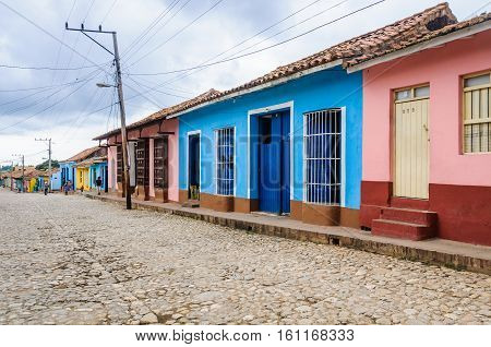 TRINIDAD, CUBA - MARCH 23, 2016: Blue and pink houses on the cobblestone streets in the UNESCO World Heritage old town of Trinidad Cuba