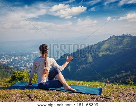 Hatha yoga outdoors - woman doing yoga asana Parivrtta Marichyasana (or ardha matsyendrasana) - seated spinal twist outdoors in mountains in morning. Vintage retro effect filtered hipster style image.