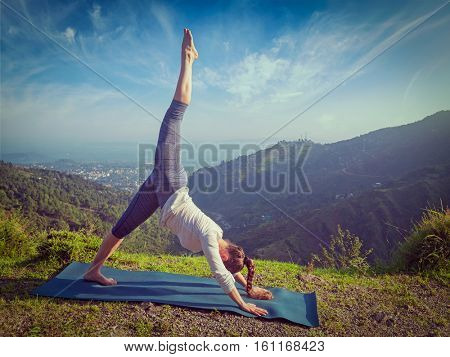 Young sporty fit woman doing yoga asana Adho mukha svanasana - downward facing dog variation outdoors in Himalayas in the morning. Vintage retro effect filtered hipster style image.