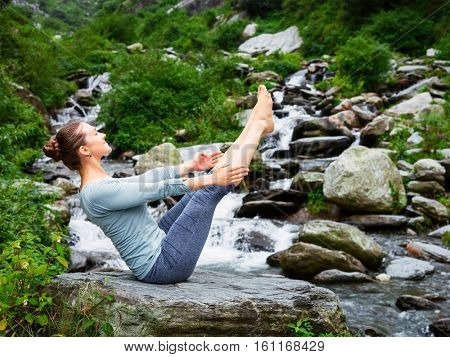 Yoga outdoors - young sporty fit woman doing Ashtanga Vinyasa Yoga asana Navasana - boat pose  - in Himalayas at waterfall. Himachal Pradesh, India. Vintage retro effect filtered hipster style image.
