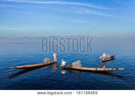 Myanmar travel attraction landmark - Traditional Burmese fishermen with fishing nets on boats at Inle lake in Myanmar famous for their distinctive one legged rowing style