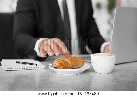 Male hand taking tasty pasty from plate, close up view