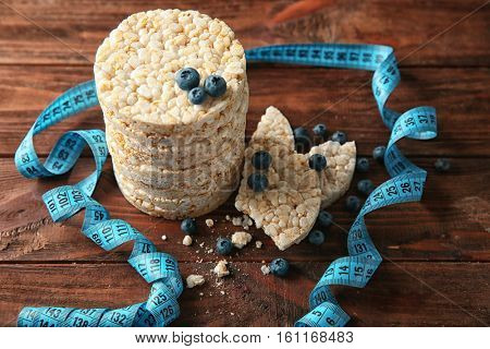 Round rice crispbreads with blueberries and measuring tape on wooden background