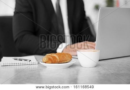 Cup of coffee and plate with tasty pasty on table, close up view