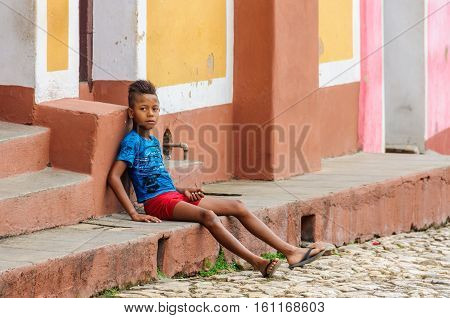 TRINIDAD, CUBA - MARCH 23, 2016: Kid sitting on the stairs of a house on the cobblestone streets in the UNESCO World Heritage old town of Trinidad Cuba