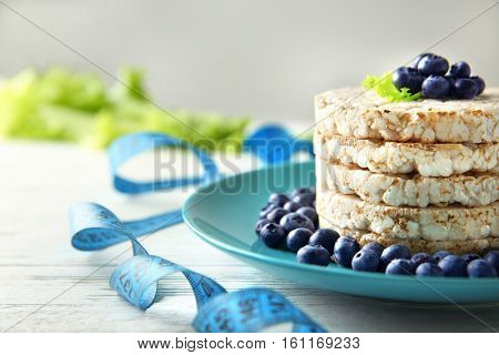 Round rice crispbreads with blueberries and measuring tape on table, closeup