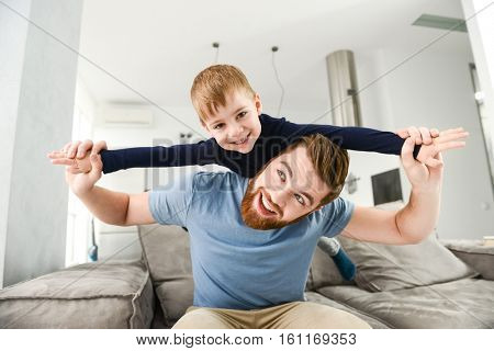 Photo of happy bearded father dressed in blue t-shirt playing with his little cute son in room