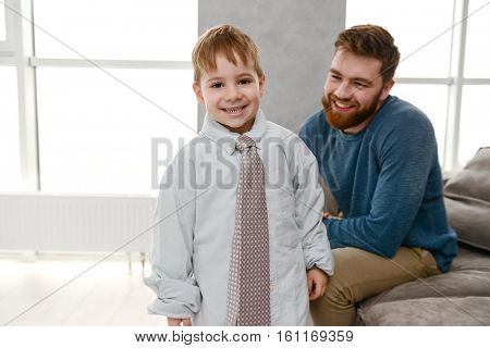 Little cute boy dressed in father's clothes smiling and look at camera.