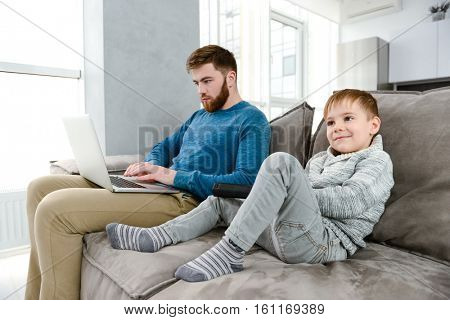 Photo of bearded young father dressed in blue sweater using laptop while his son watching TV.