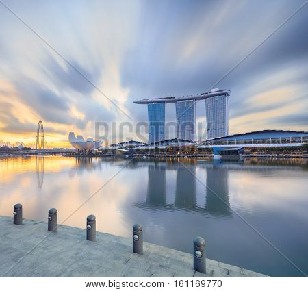 Singapore, Republic of Singapore - May 4, 2016: Marina Bay Sands hotel reflecting in sunrise water with steps on foreground