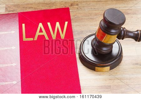 Wooden Law Gavel and legal book with word Law close up on wooden desktop, top view