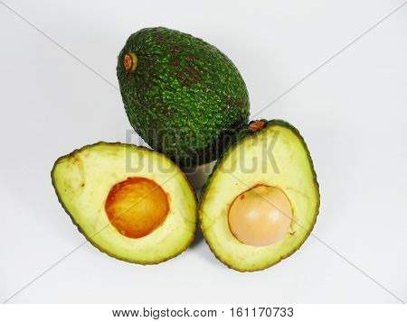 Avocado isolated on white,Close-up of an avocado and avocado oil on wooden table. Healthy food concept.