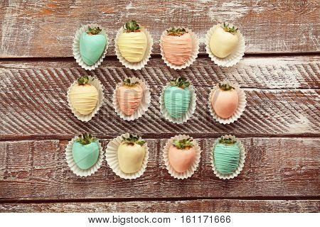 Strawberries covered with colorful chocolate icing on wooden background
