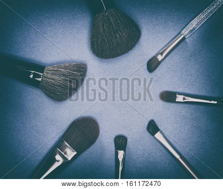 Set of various natural bristle makeup brushes: for applying blush, powder, foundation, cream and compact eyeshadow on blue background. Copy space. Retro style processing