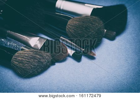 Set of various make up brushes on blue background. Professional tools of makeup artist. Selective focus. Retro style processing