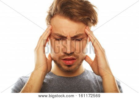Terrible headache. Young business man touching his head and keeping eyes closed while standing isolated on  white background