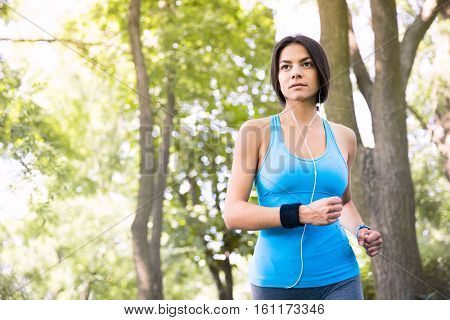 Sporty young woman running outdoors in park. Looking away