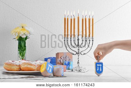 Beautiful composition for Hanukkah on wooden table against textured wall