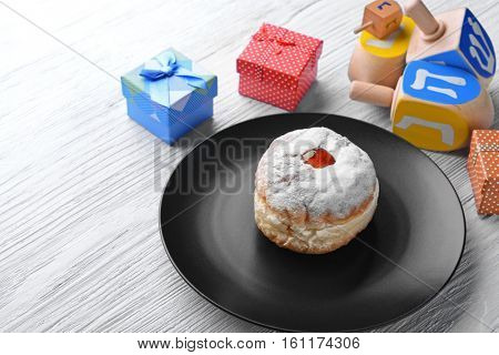 Composition of tasty donut, dreidels and presents for Hanukkah on light wooden table