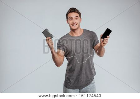 Smiling casual man charging his mobile phone isolated on the white background