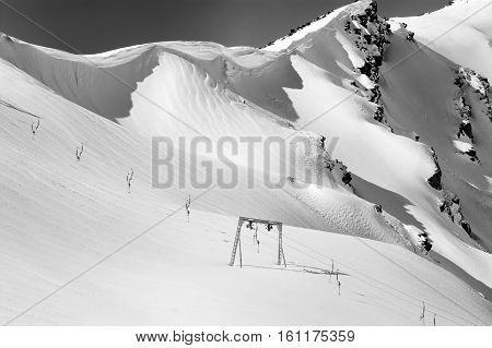 Black and white view on old surface lift and mountains with snow cornice. Mount Cheget. Caucasus Mountains. Elbrus region.