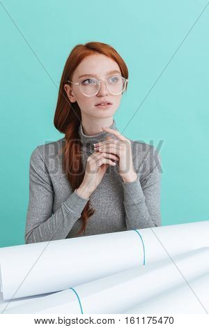 Thoughtful beautiful young woman in round glasses sitting at the table with blueprints over blue background