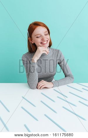 Cheerful young woman with pencil behind ear sitting and smiling over blue background