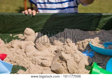Playground with kinetic sand outdoors. Child playing with shapes.