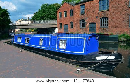Blue boat on the Birmingham old canal in a sunny Summer day .