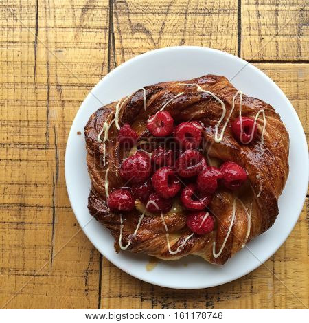Start your day with homemade Gourmet danish pastry raspberry and icing on the wood table
