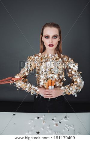 Portrait of beautiful addicted young woman holding syringes with drugs