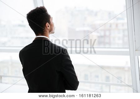 Back view of African business man in black suit looking at window in office
