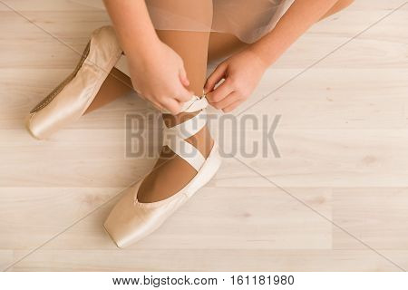 Legs of young ballerina ballet dancing. A photo of ballerina tying Pointe shoes pointes.