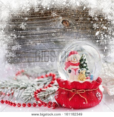 A Snow Globe With Snowman On The Snow-covered Wooden Background