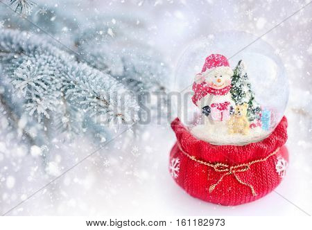 A Snow Globe With Snowman On A Background Snow-covered Fir Branches